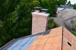CertainTeed's Winter Guard installed around the Chimney by Dennison Exterior Solutions & Gutter Topper